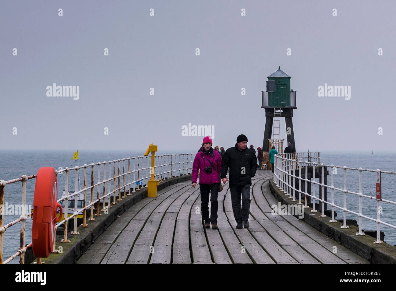 People in warm clothes, walking on Whitby's West Pier Extension, England, UK  - grey wooden boards, sea and - Stock Image