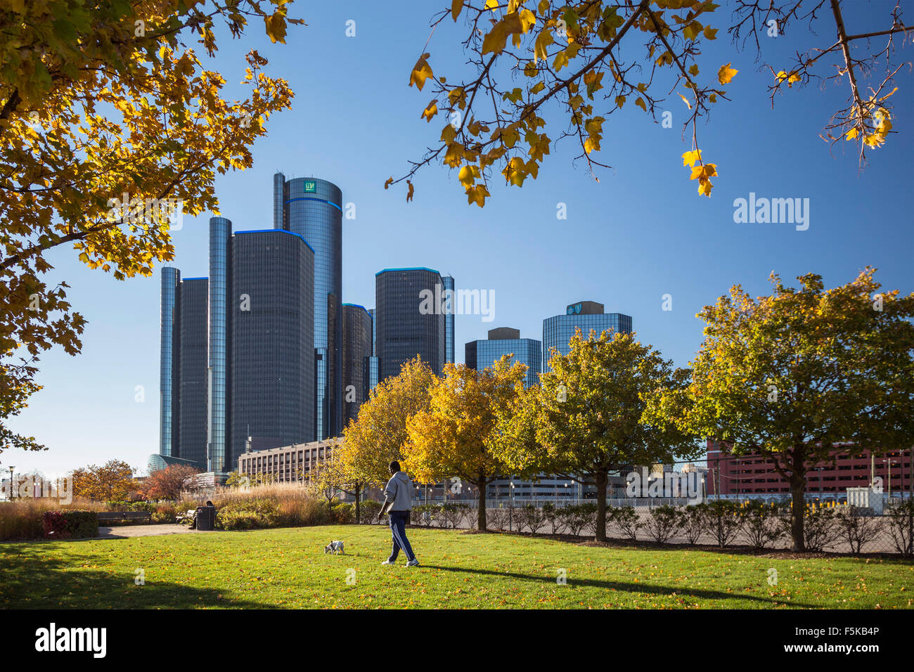 Detroit, Michigan - A man walks his dog near the Renaissance Center, which houses the General Motors headquarters. - Stock Image