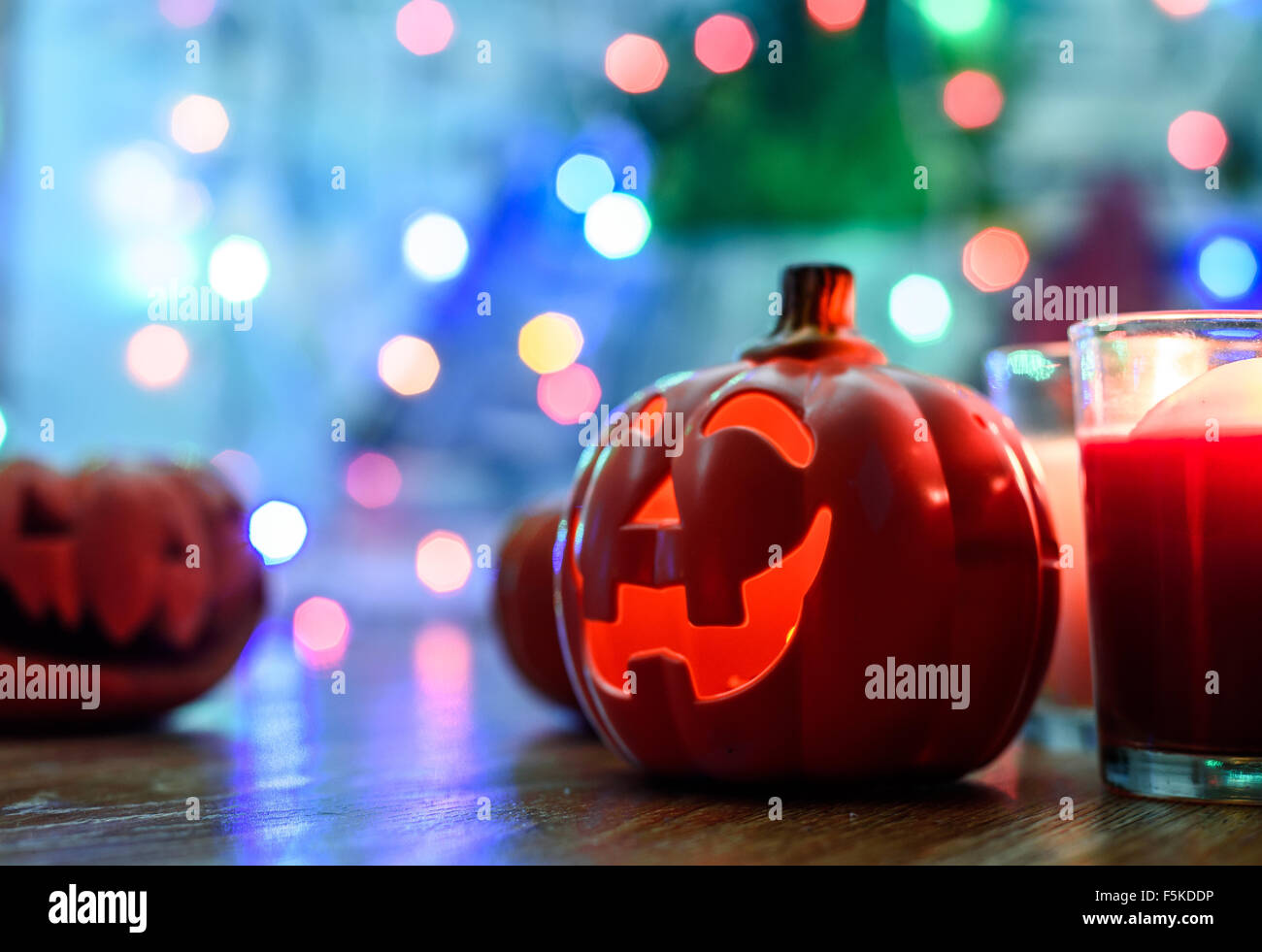 Halloween Pumpkins and candel on the wooden and colorful bokeh background - Stock Image