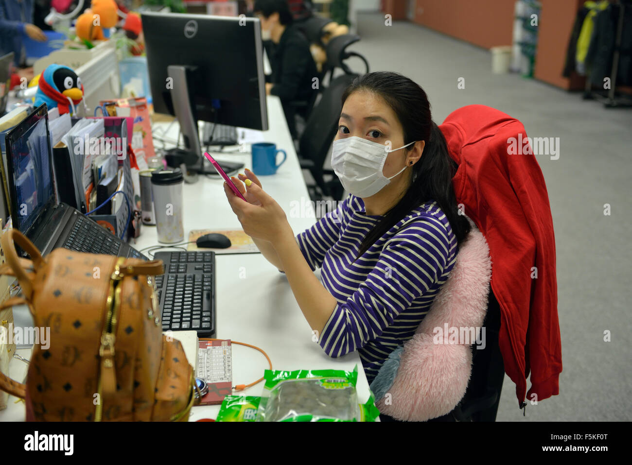 A lady wears mask while working in office in Beijing. Some people have to wear masks when severe smog hits Beijing. - Stock Image