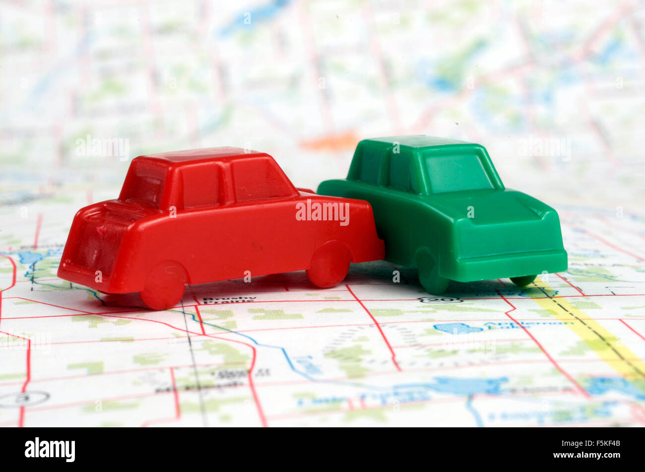 Collision of Two Plastic Play Cars On A Map - Stock Image