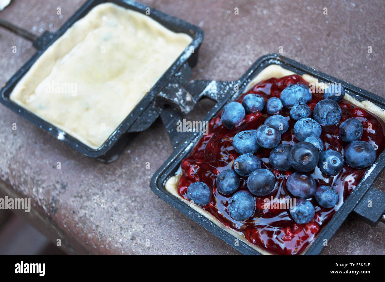 Opened Hobo, or Camp Pie Before Cooking Made Of Blueberries - Stock Image