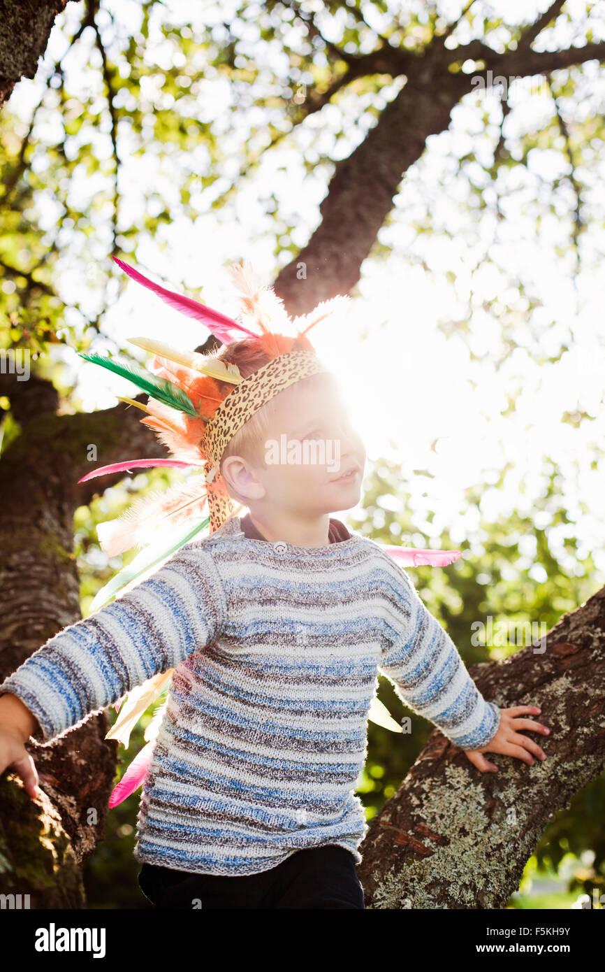 Sweden, Sodermanland, Strangnas, Boy (4-5) wearing plume in sunlight - Stock Image