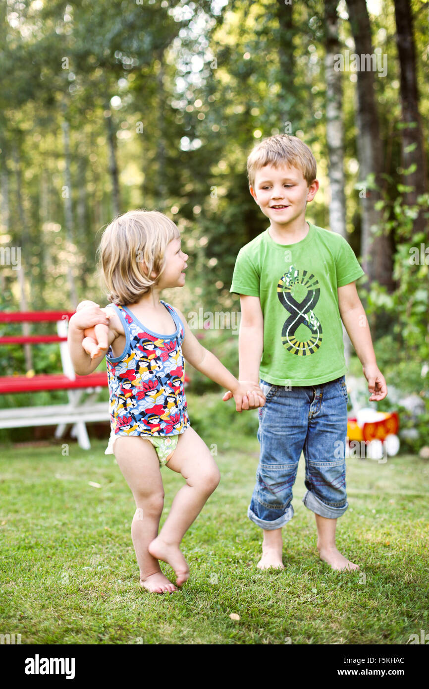 Sweden, Narke, Hallsberg, Boy (4-5) and girl (2-3) holding hands - Stock Image