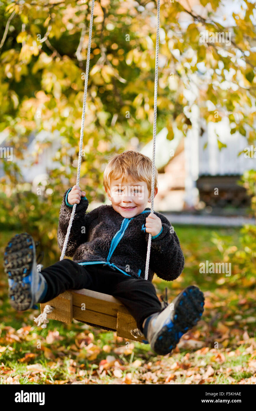 Sweden, Sodermanland, Strangnas, Boy (4-5) playing on swing in garden - Stock Image