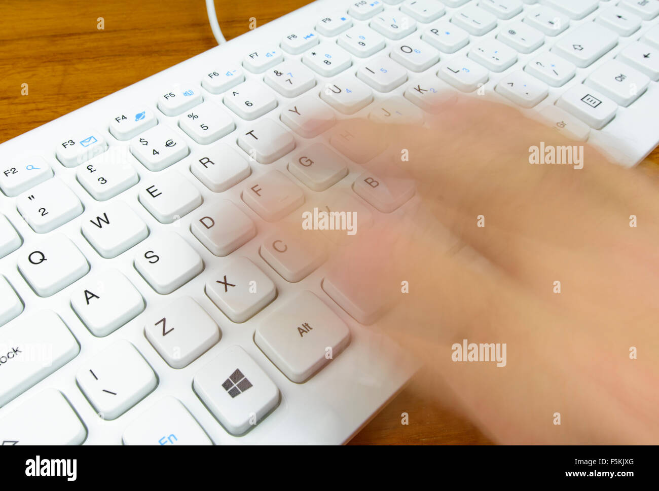 Typing fast on a computer keyboard, with the typists hand blurred to infer speed. - Stock Image