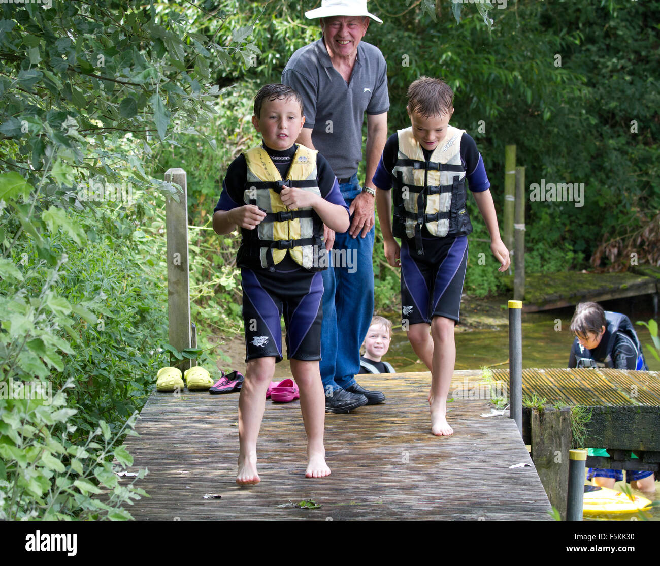 Children in life Jackets buoyancy aids wet suits - Stock Image