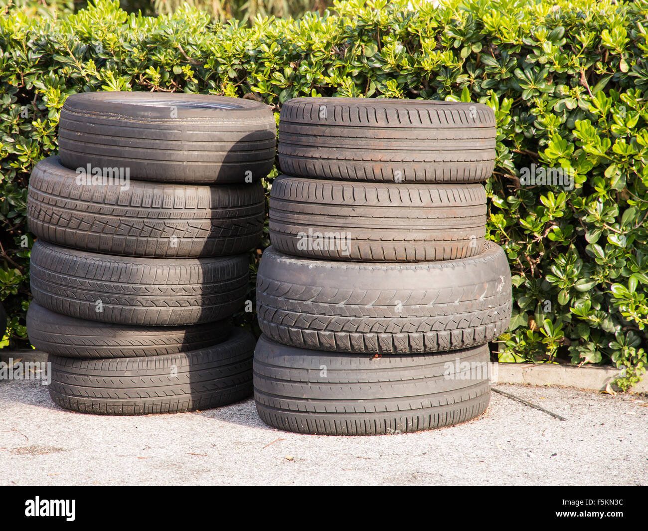 Pile of used worn out tyres green bushes in background - Stock Image