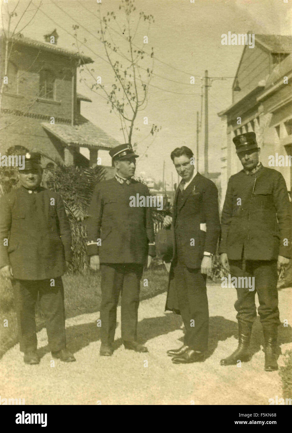 Three soldiers and a civilian at the Milan Fair 1926, Italy - Stock Image