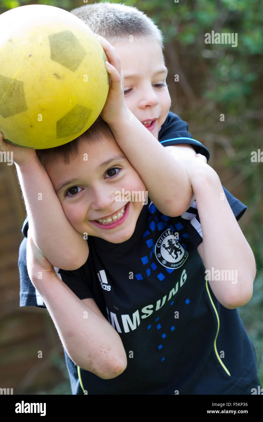 Boys playing with a ball having  a piggy back ride carried lift - Stock Image