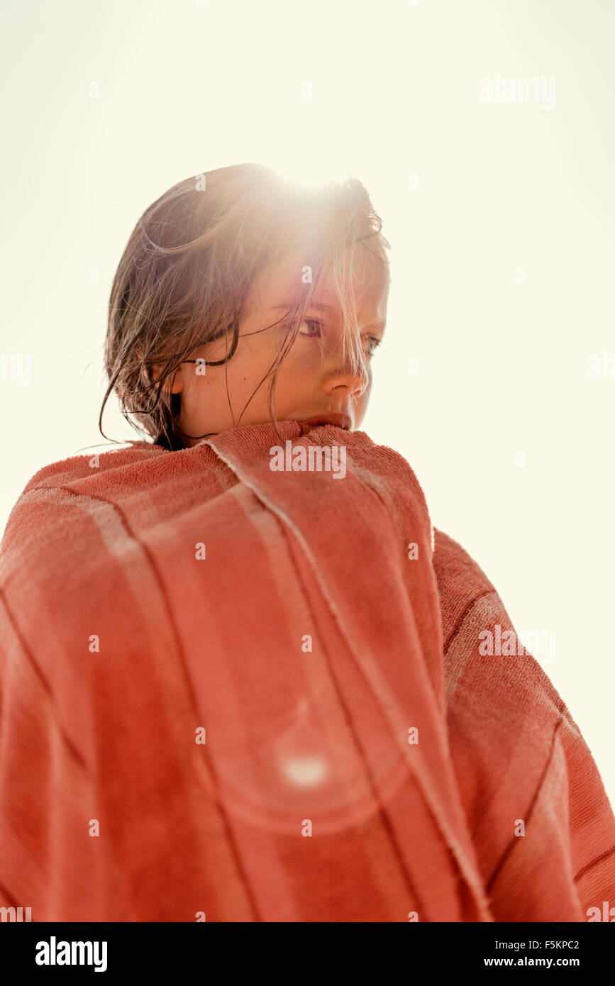 Sweden, Smaland, Tjust archipelago, Vastervik, Hasselo, Girl (8-9) wrapped in towel against sky - Stock Image