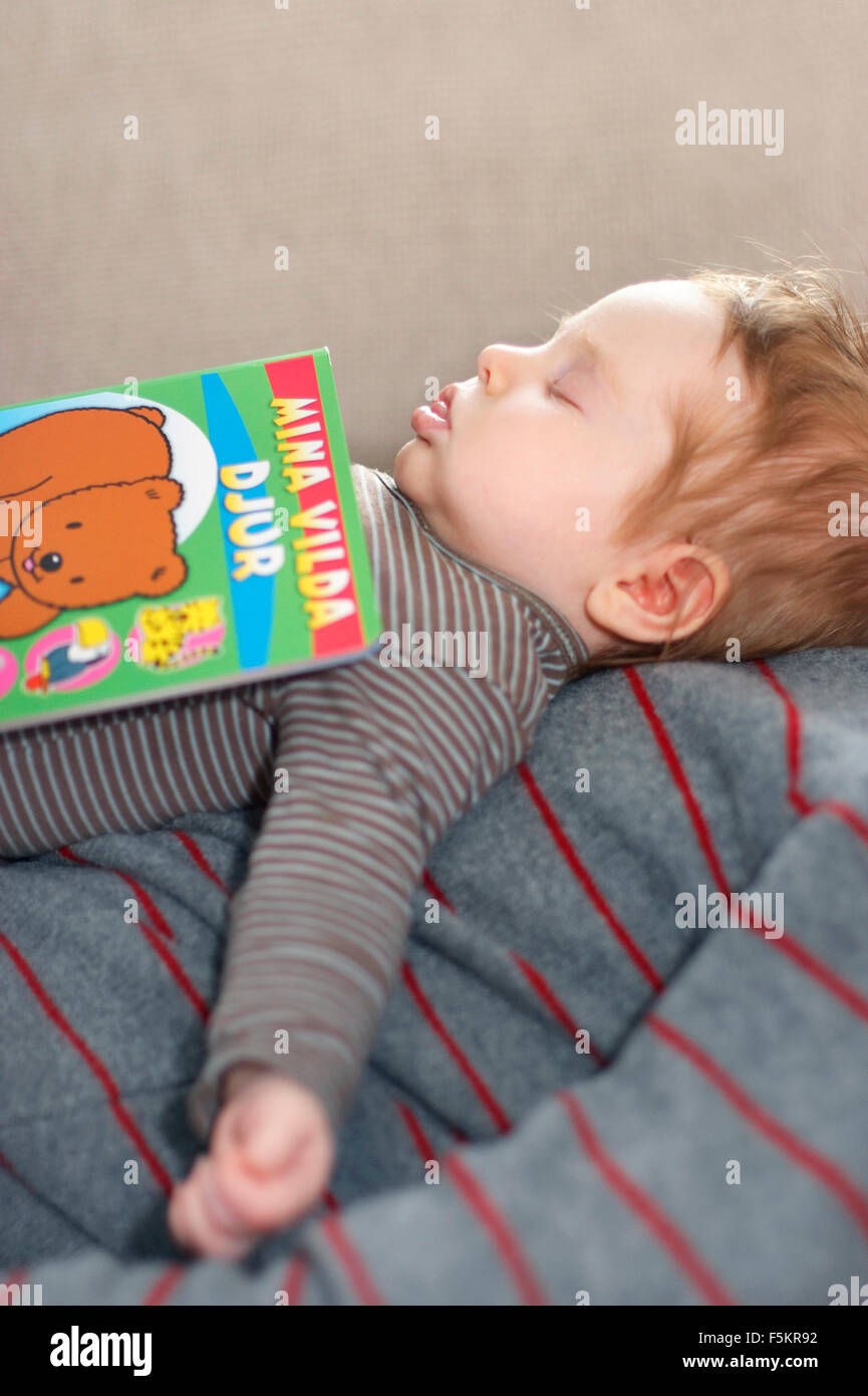Sweden, Vastra Gotaland, Gothenburg, Girl (12-17 months) sleeping with book on father's chest - Stock Image