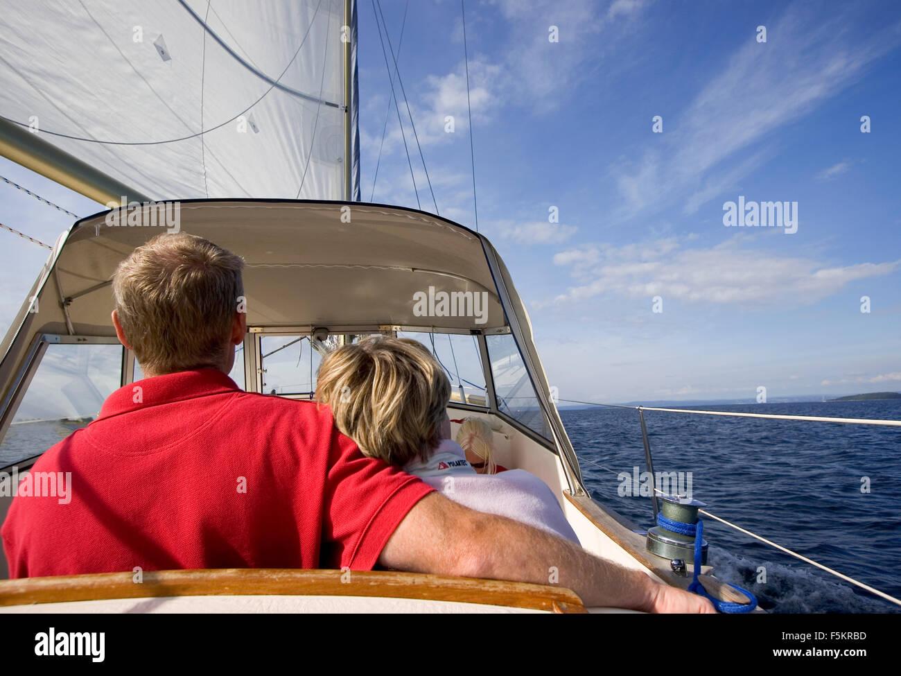 Sweden, Bohuslan, Reare view of sailing couple - Stock Image