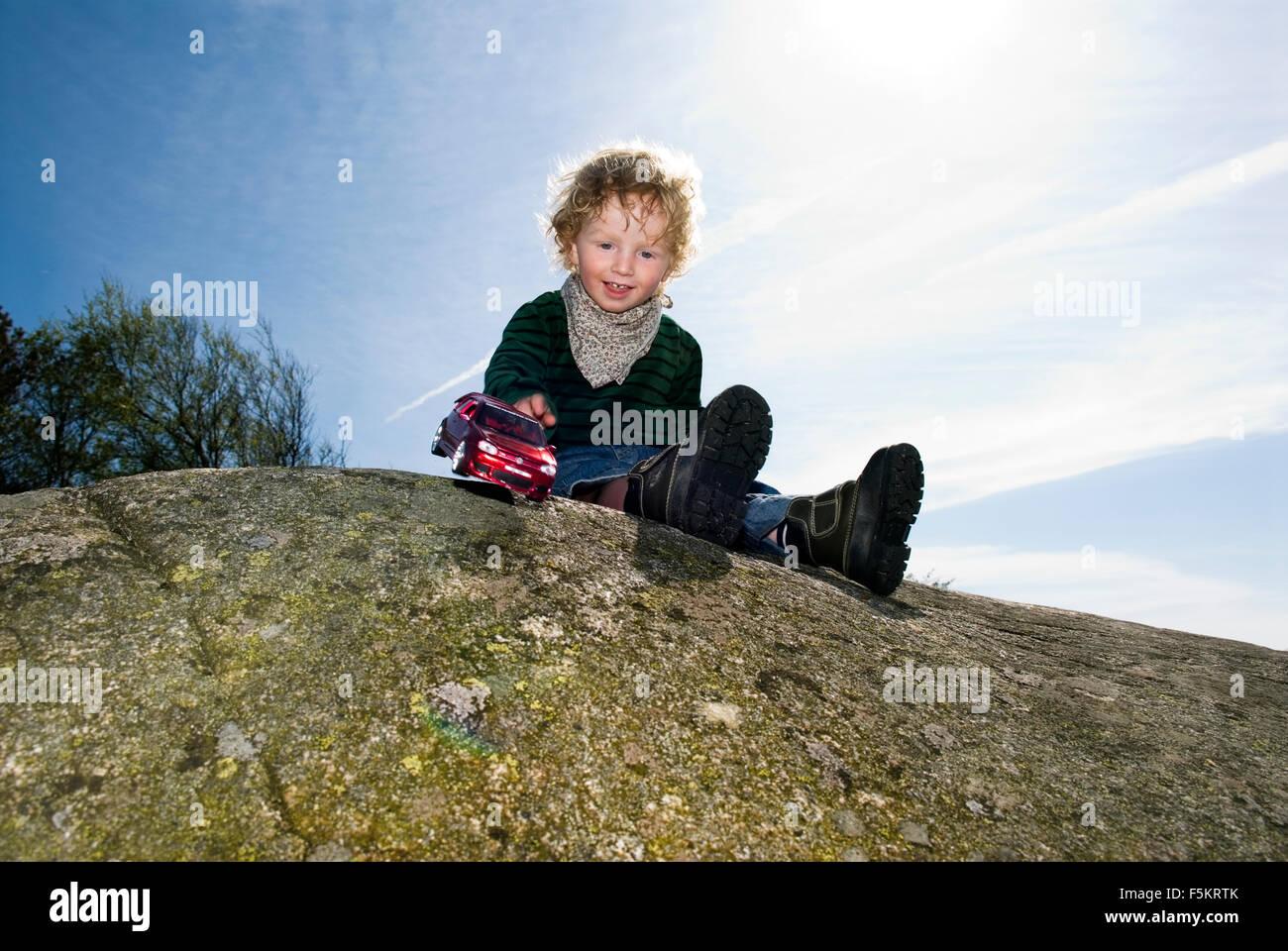 Sweden, Bohuslan, Boy (4-5) playing on rock - Stock Image