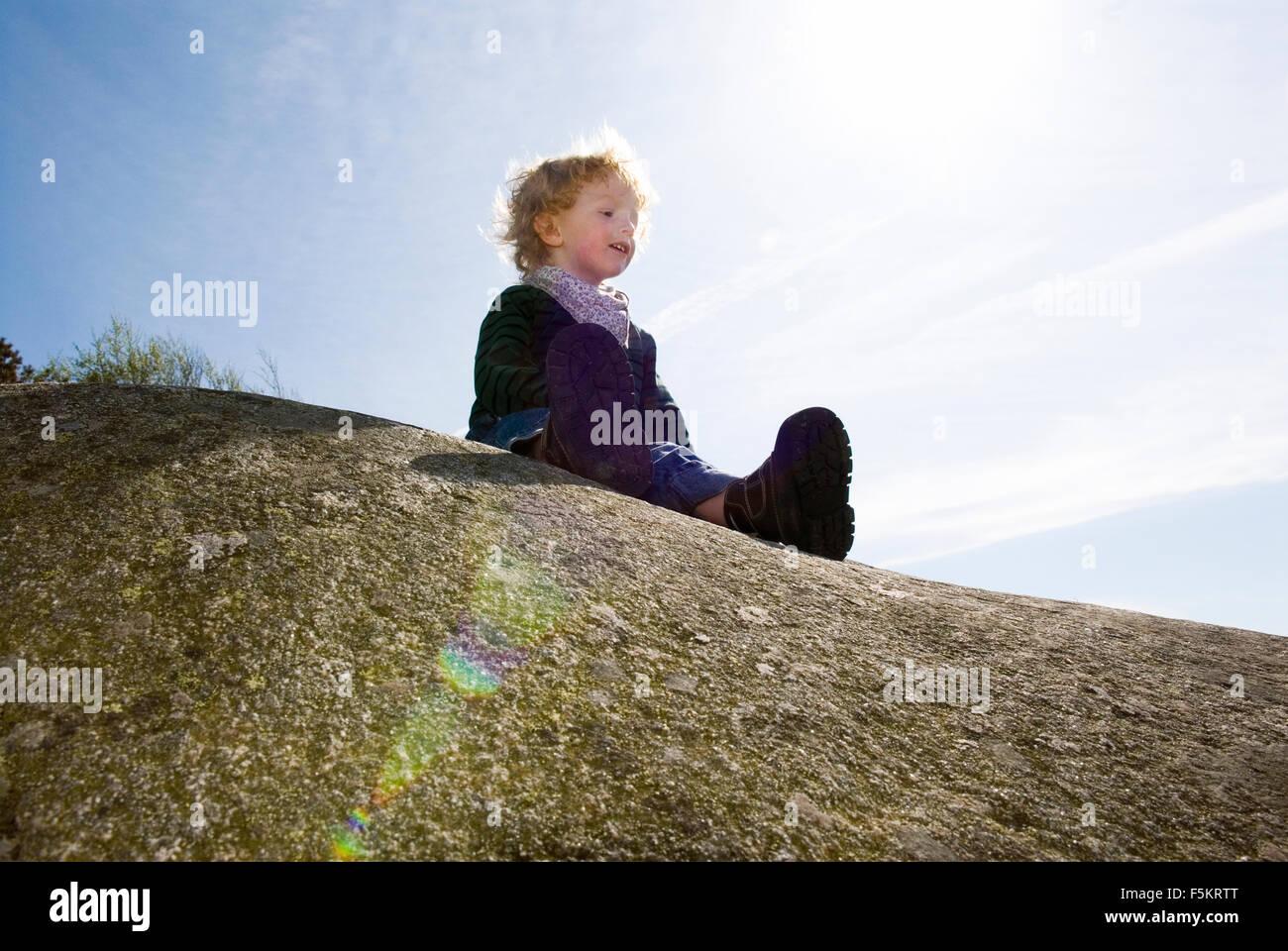 Sweden, Bohuslan, Boy (4-5) sitting on rock - Stock Image