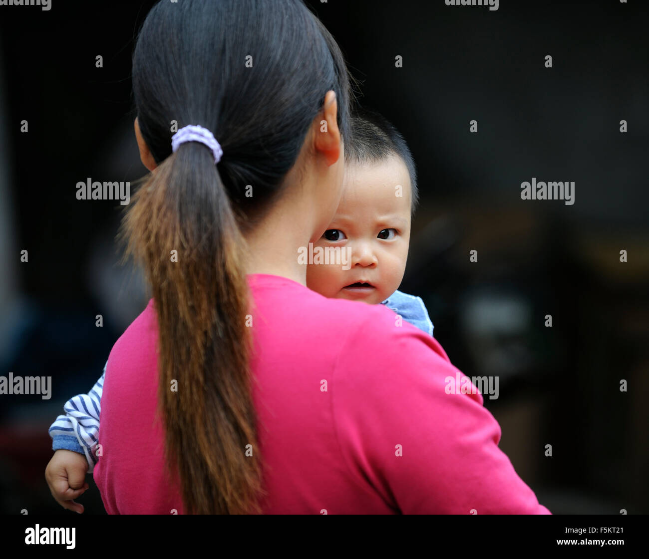 A Chinese mother holds her baby in Beijing, China. - Stock Image