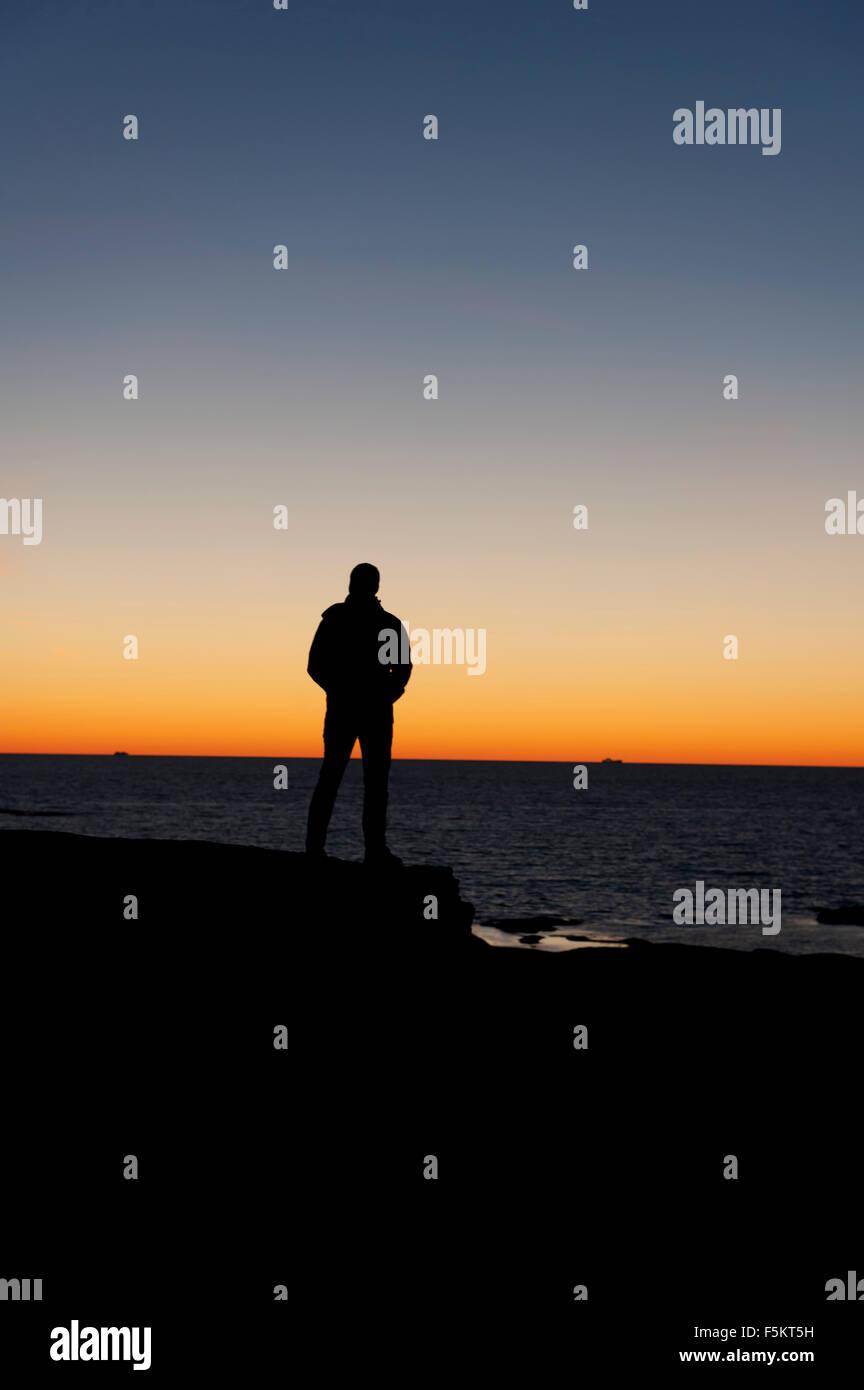 Sweden, Bohuslan, Silhouette of man standing on beach at dusk - Stock Image