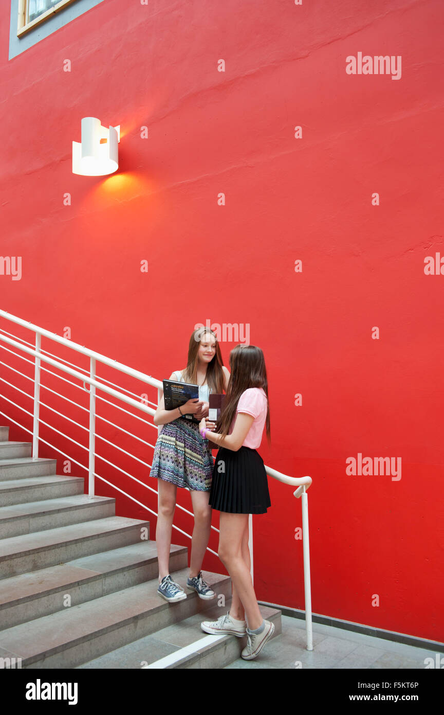 Sweden, Gotaland, Teenage girls (14-15) talking outside school - Stock Image