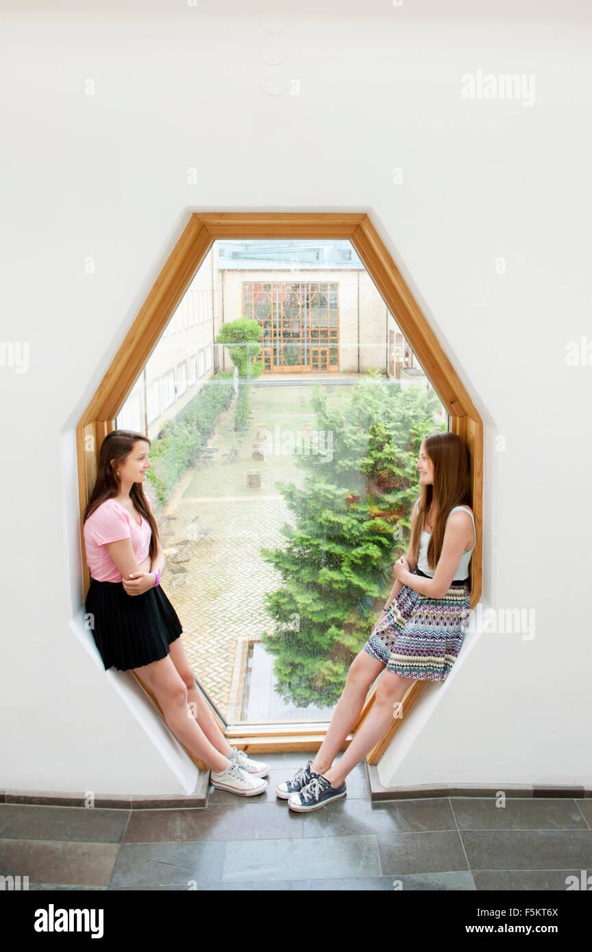 Sweden, Girls (14-15) leaning against window frame, talking - Stock Image