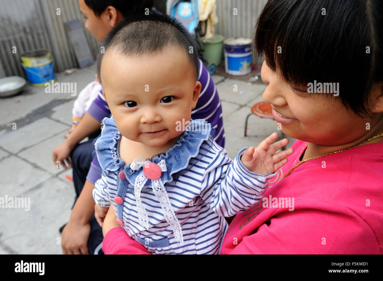 A Chinese woman holds a baby in Beijing, China. - Stock Image