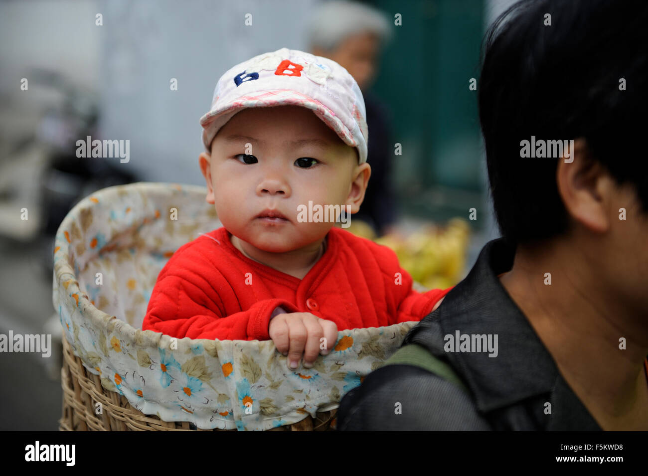 A Chinese woman holds a baby with a bamboo basket in Beijing, China. - Stock Image