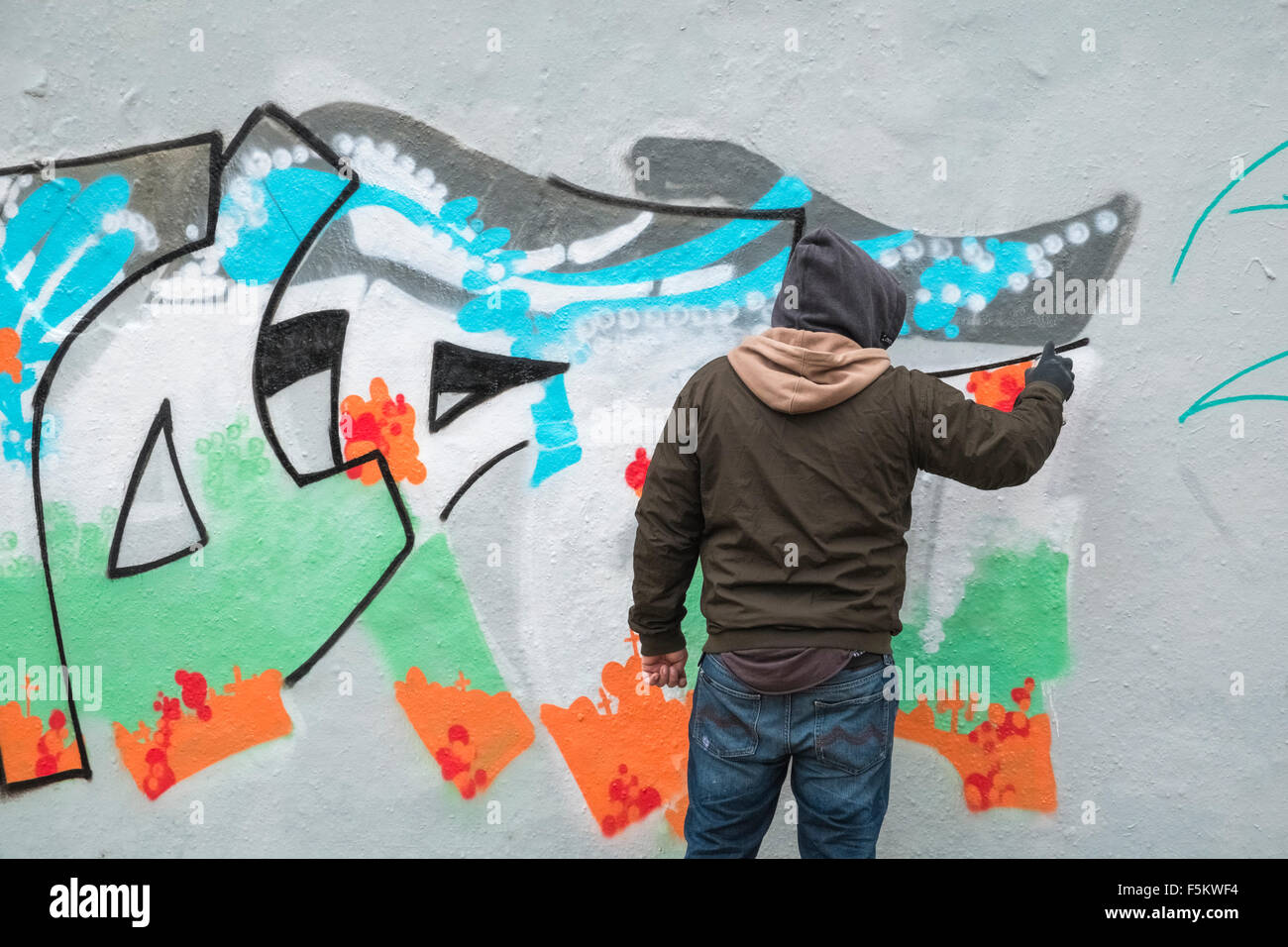 Graffiti artist spray painting part of former berlin wall mauerpark prenzlauer berg berlin