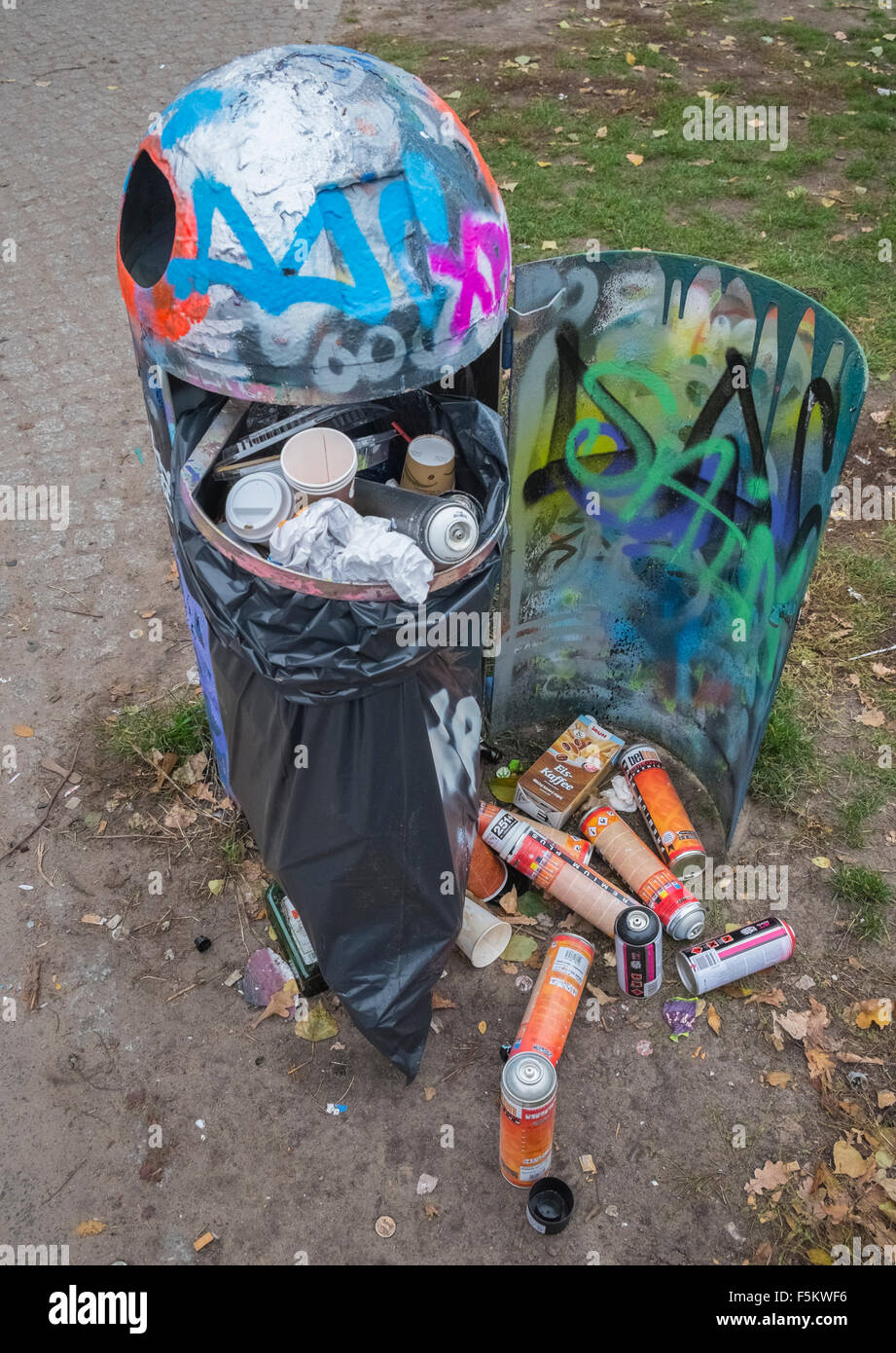 Used paint spray cans in refuse container Stock Photo