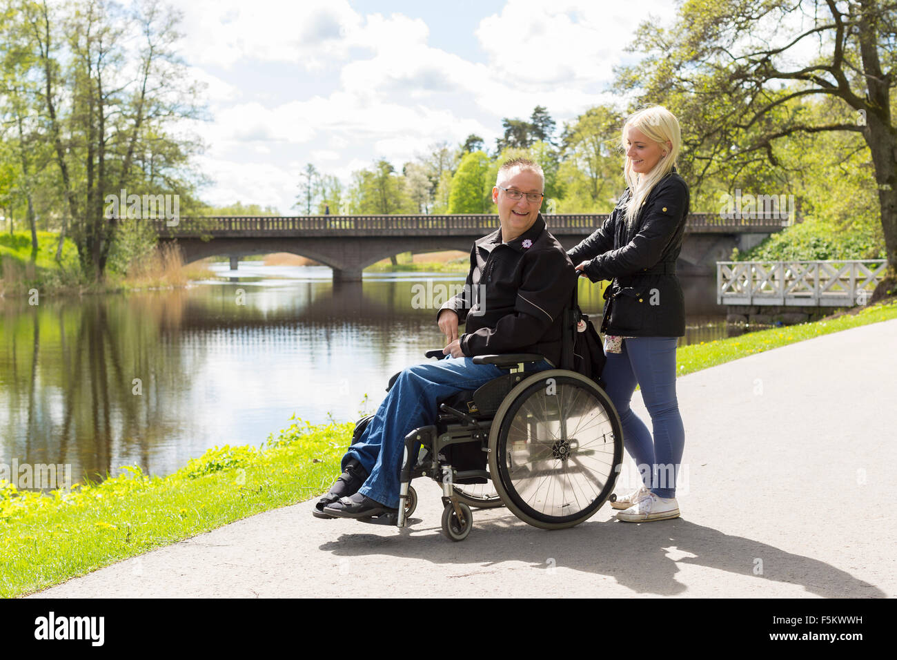 Sweden, Ostergotland, Mjolby, Man on wheelchair with personal assistant in park - Stock Image