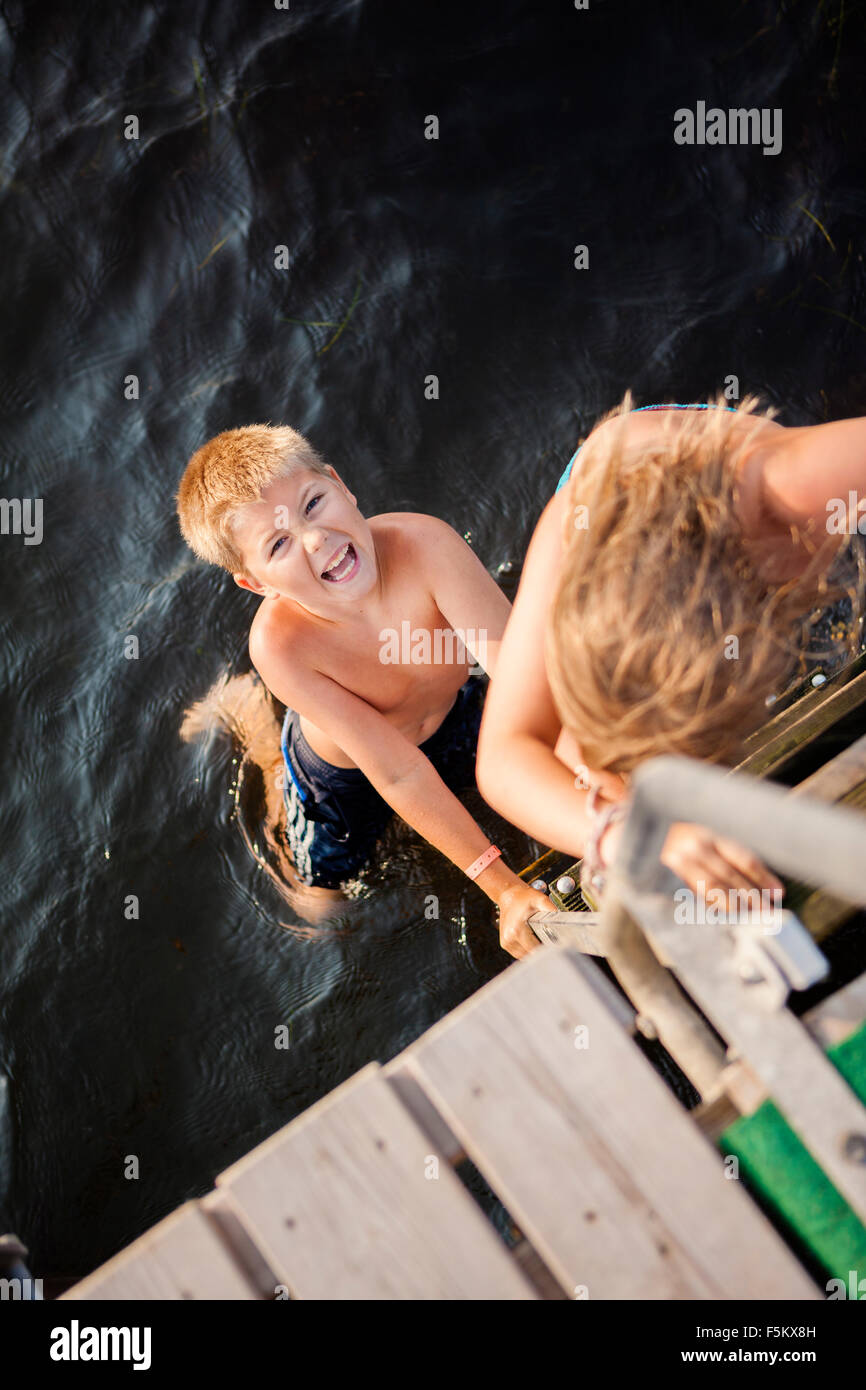 Sweden, Oland, Gronhogen, Brother (10-11) and sister (6-7) chasing each other - Stock Image