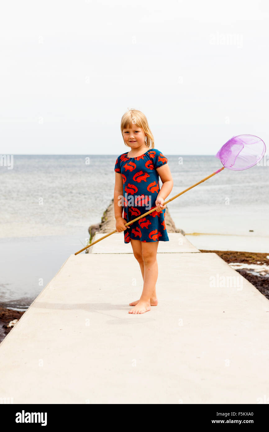 Sweden, Oland, Gronhogen, Girl (6-7) standing on jetty with fishing net - Stock Image