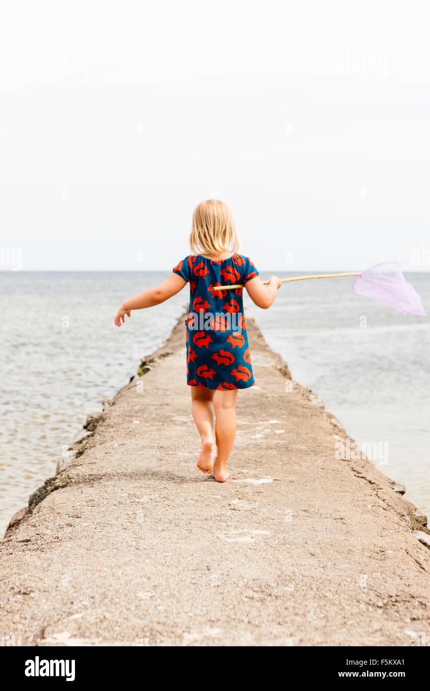 Sweden, Oland, Gronhogen, Rear view of girl (6-7) holding fishing net - Stock Image