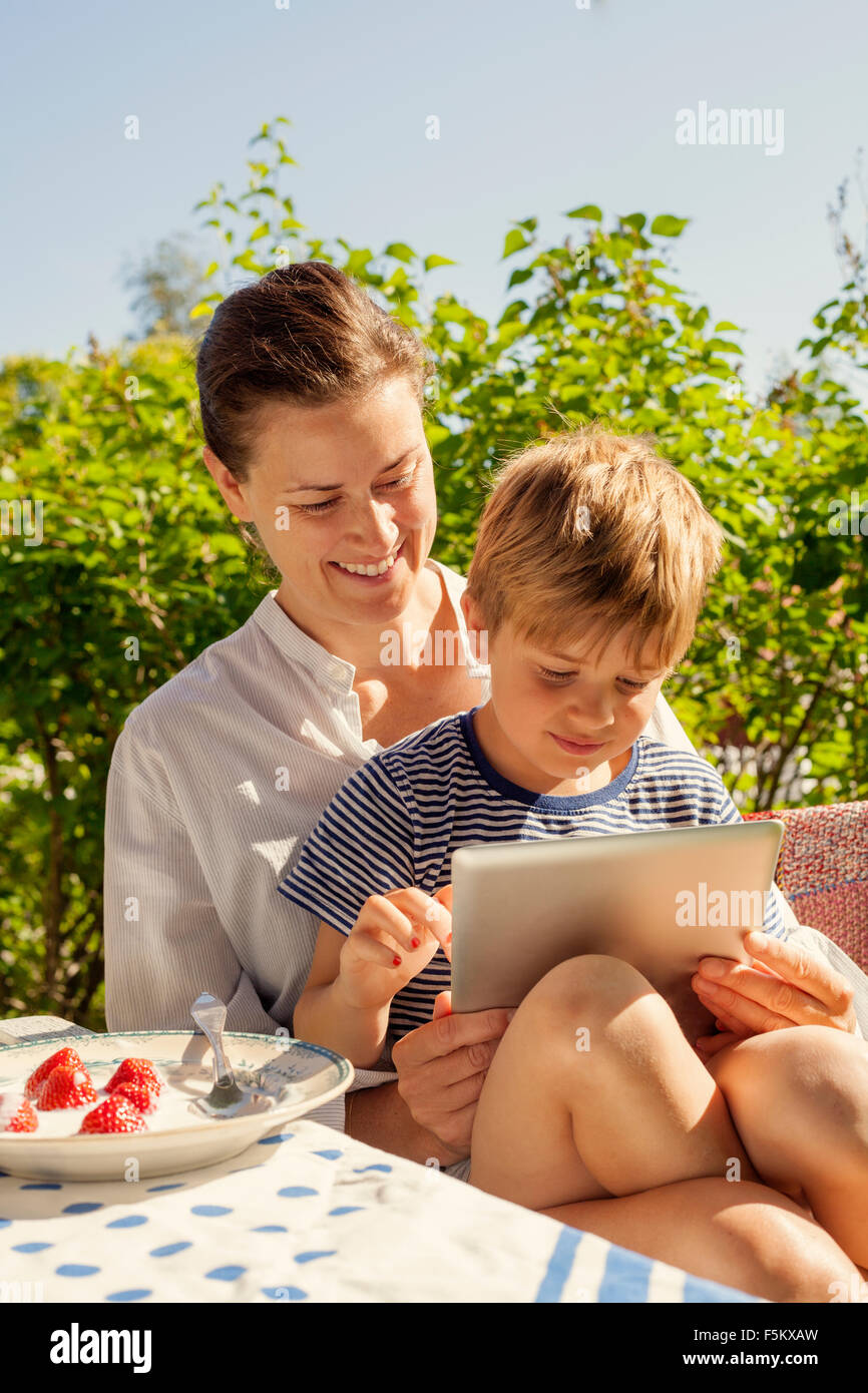 Sweden, Halsingland, Jarvso, Picture son (4-5) and mother in garden - Stock Image