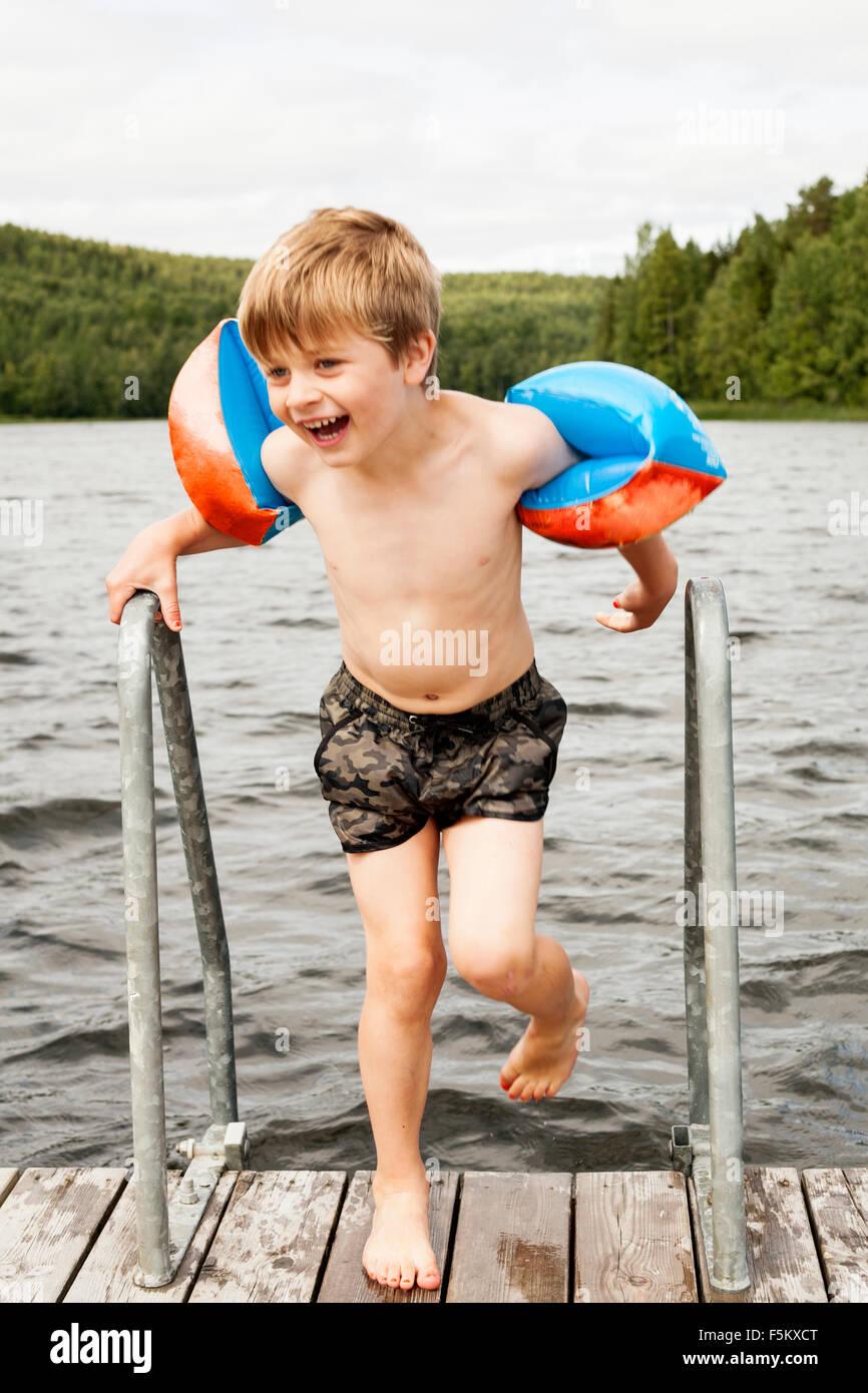 Sweden, Uppland, Runmaro, Barrskar, Portrait of boy (4-5) with water wings on jetty - Stock Image