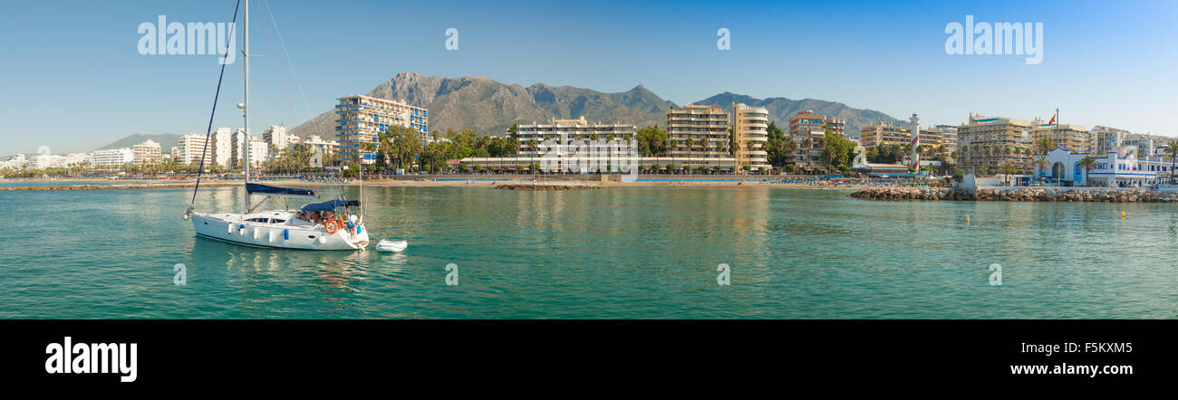 A sailing yacht leaves the port at Marina Marbella. A panoramic view of this beautiful marina on the Costa del Sol, - Stock Image