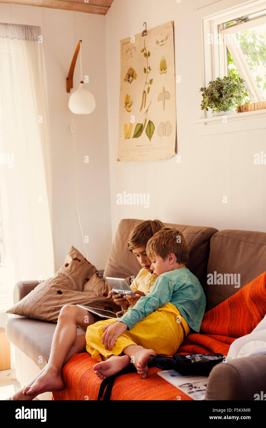 Sweden, Uppland, Runmaro, Barrskar, Brothers (4-5, 6-7) playing on game console on sofa - Stock Image