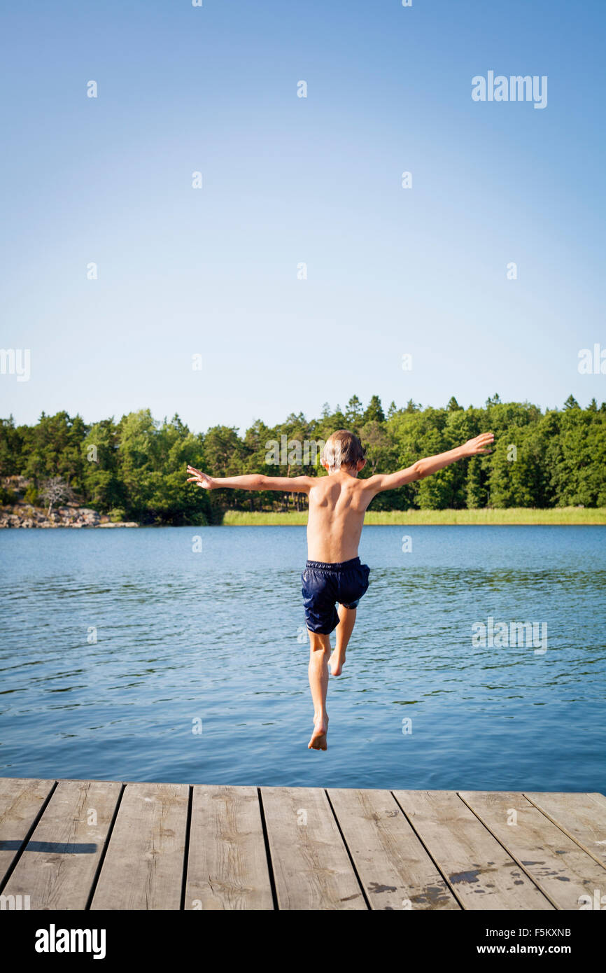 Sweden, Uppland, Runmaro, Barrskar, Rear view of boy (6-7) jumping into water from jetty - Stock Image