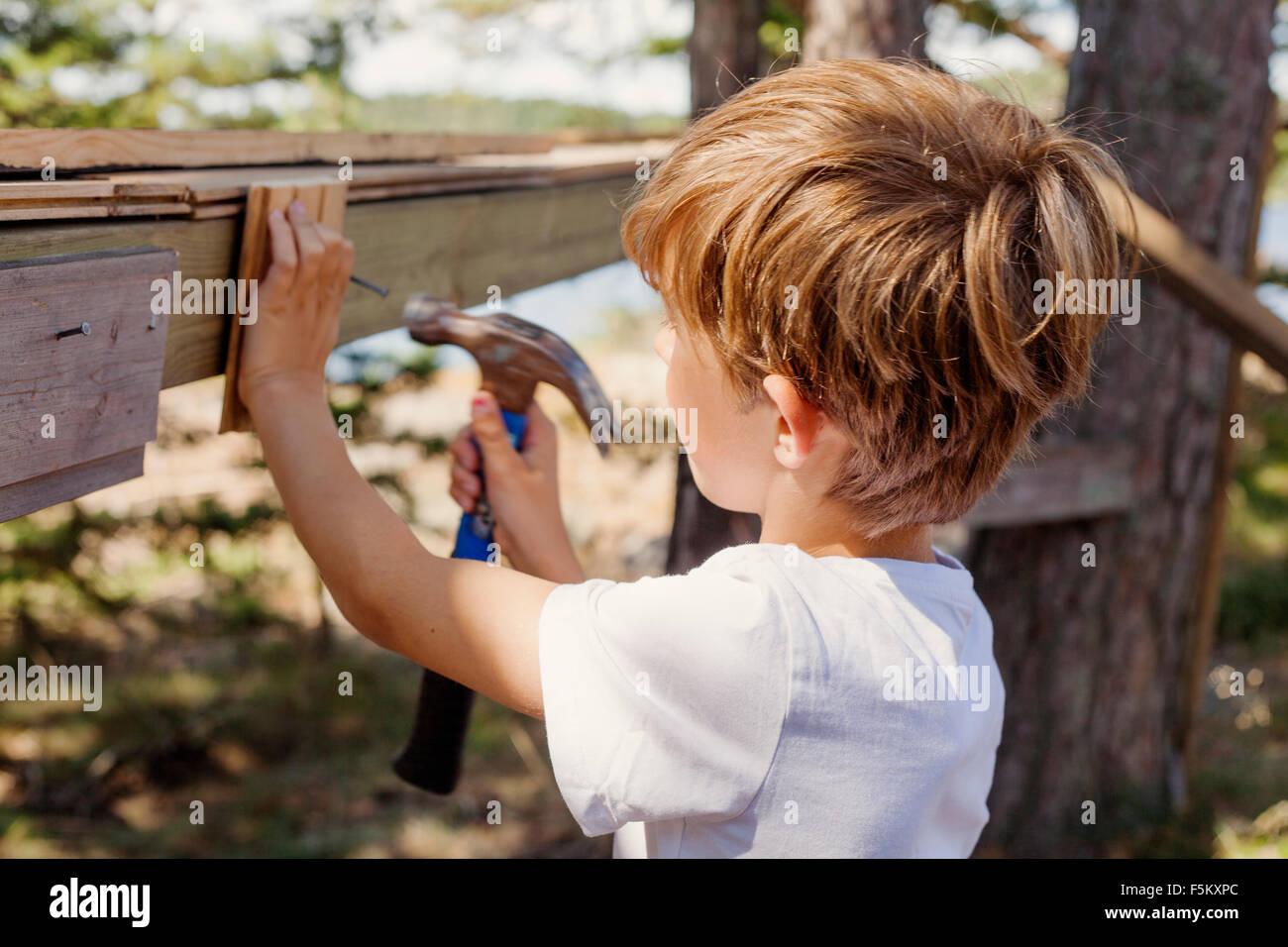 Sweden, Uppland, Runmaro, Barrskar, Boy (4-5) pounding hammer - Stock Image