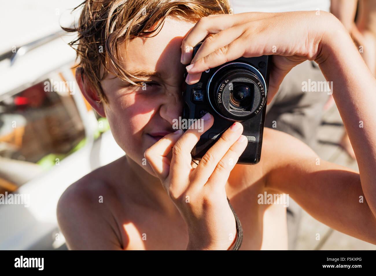 Sweden, Uppland, Runmaro, Barrskar, Portrait of boy (6-7) photographing - Stock Image