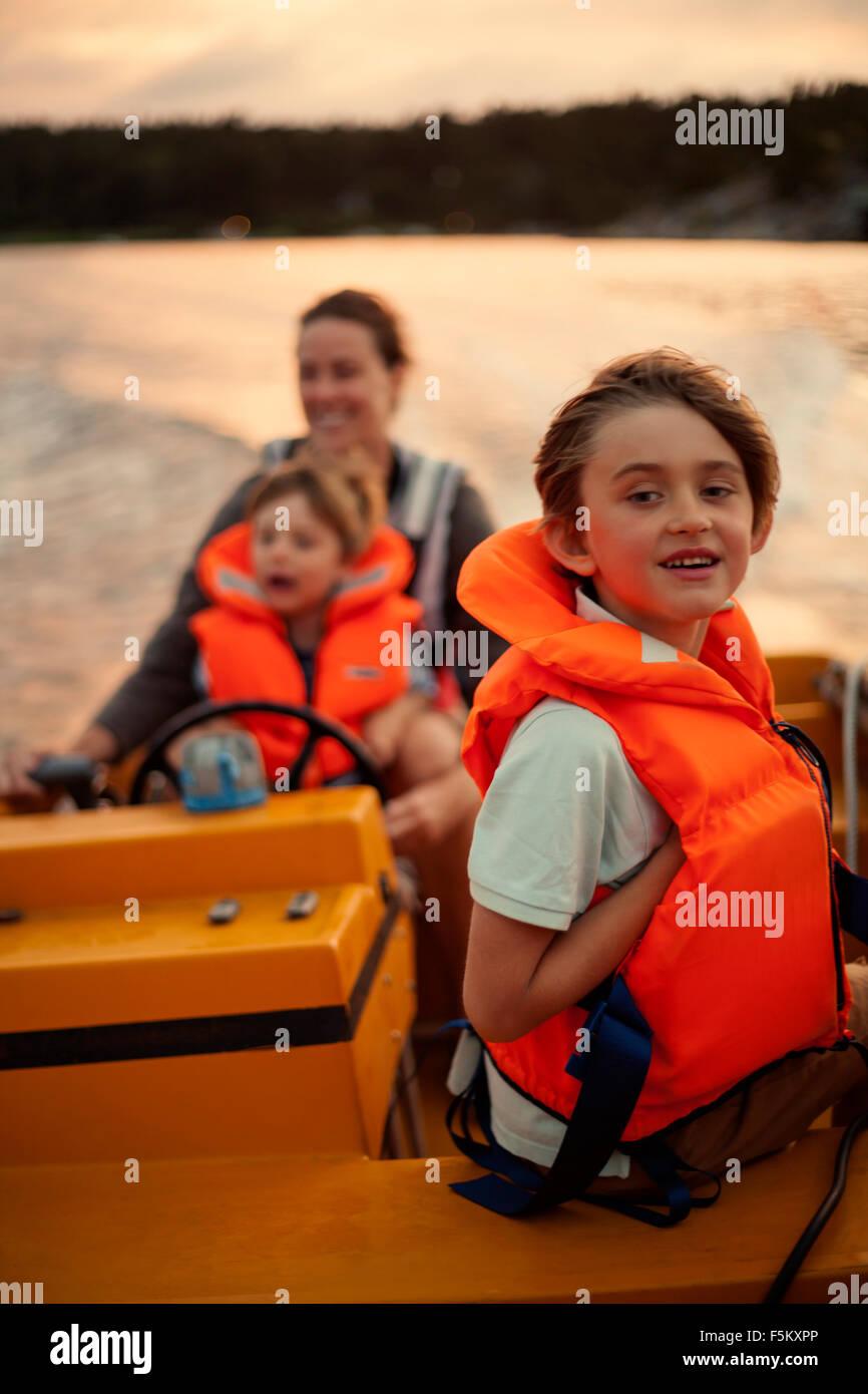 Sweden, Uppland, Runmaro, Barrskar, Mother with sons (4-5, 6-7) on motorboat - Stock Image