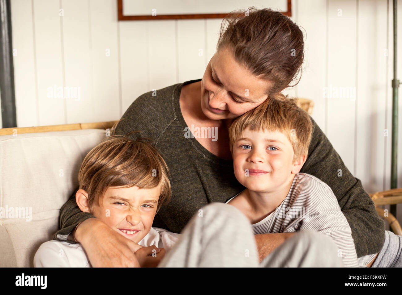 Sweden, Uppland, Runmaro, Barrskar, Portrait of mother with two sons (4-5, 6-7) Stock Photo
