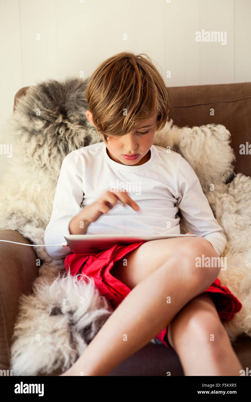 Sweden, Uppland, Runmaro, Barrskar, Boy (6-7) using digital tablet - Stock Image