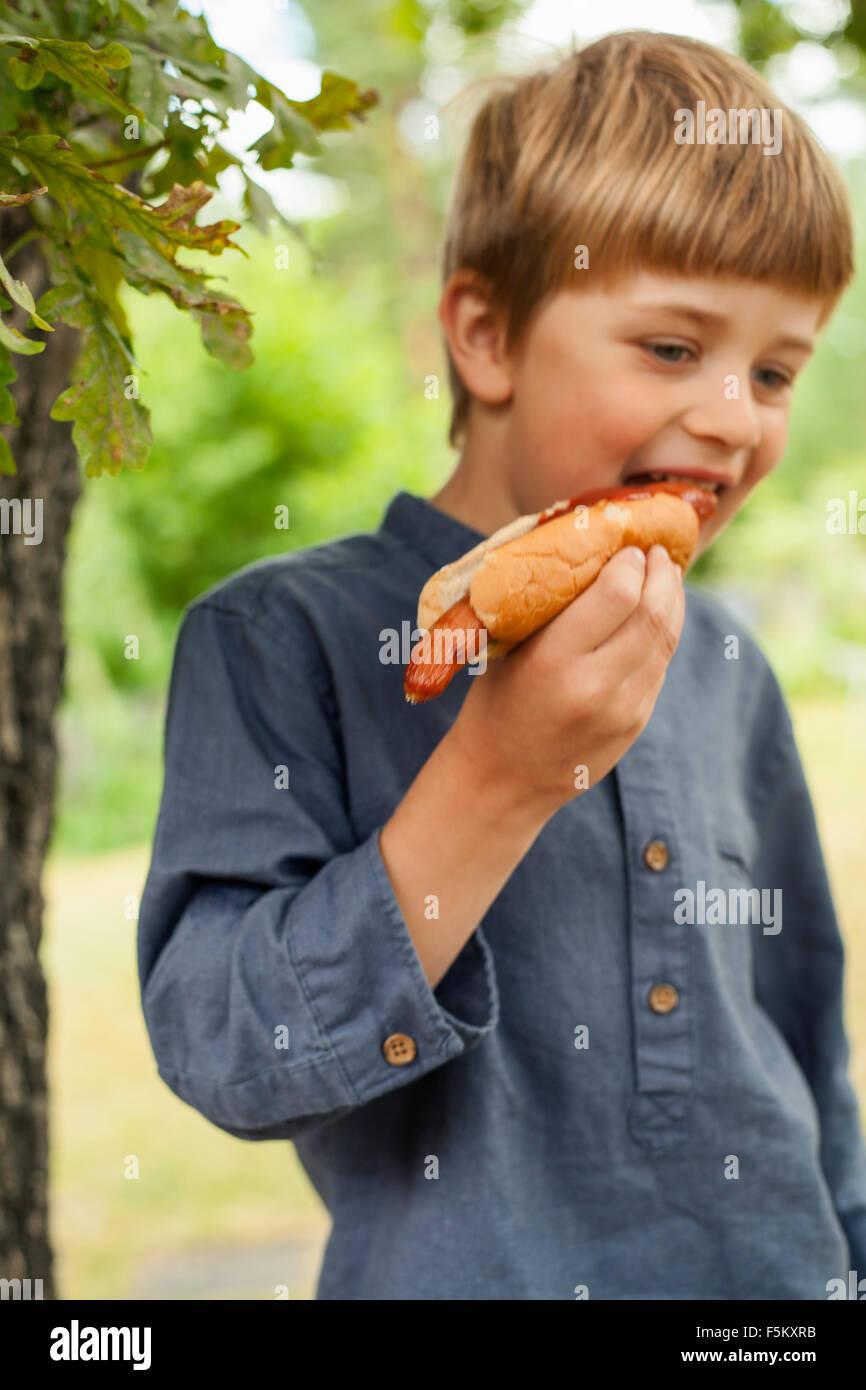 Sweden, Uppland, Runmaro, Barrskar, Portrait of boy (4-5) eating hot dog - Stock Image