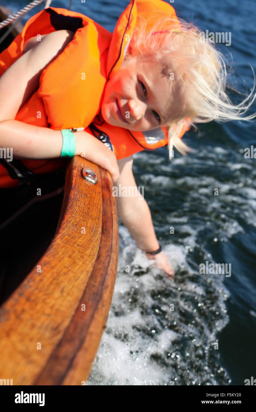 Sweden, Uppland, Runmaro, Barrskar, Girl (6-7) in sailboat - Stock Image