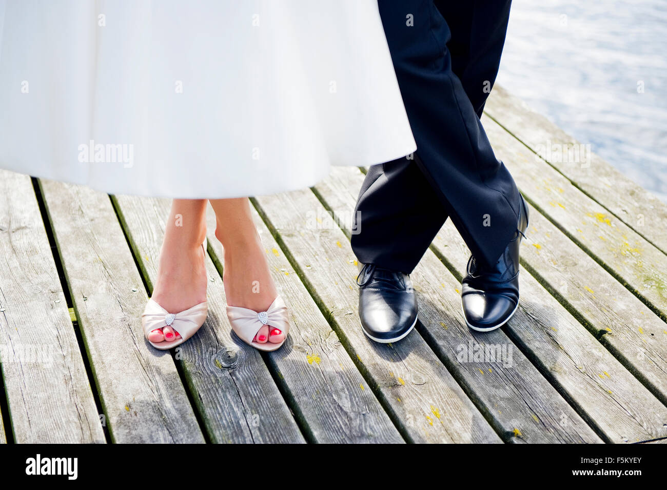 Sweden, Uppland, Arholma, Feet of man and woman standing on wooden pier Stock Photo