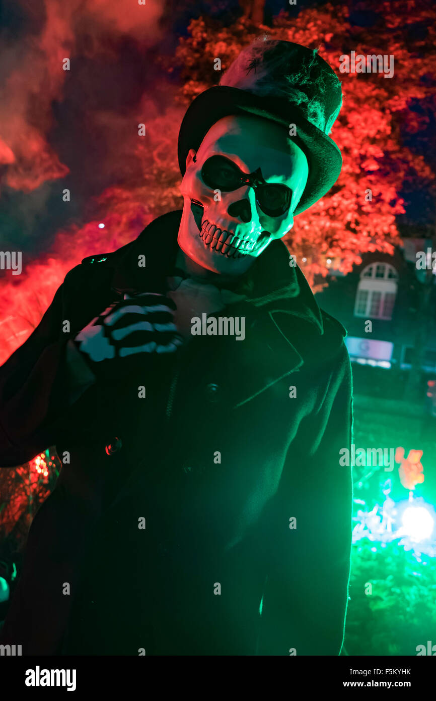 8d9ab09af4c halloween skeleton in a top hat standing in front of a tree lit up with red