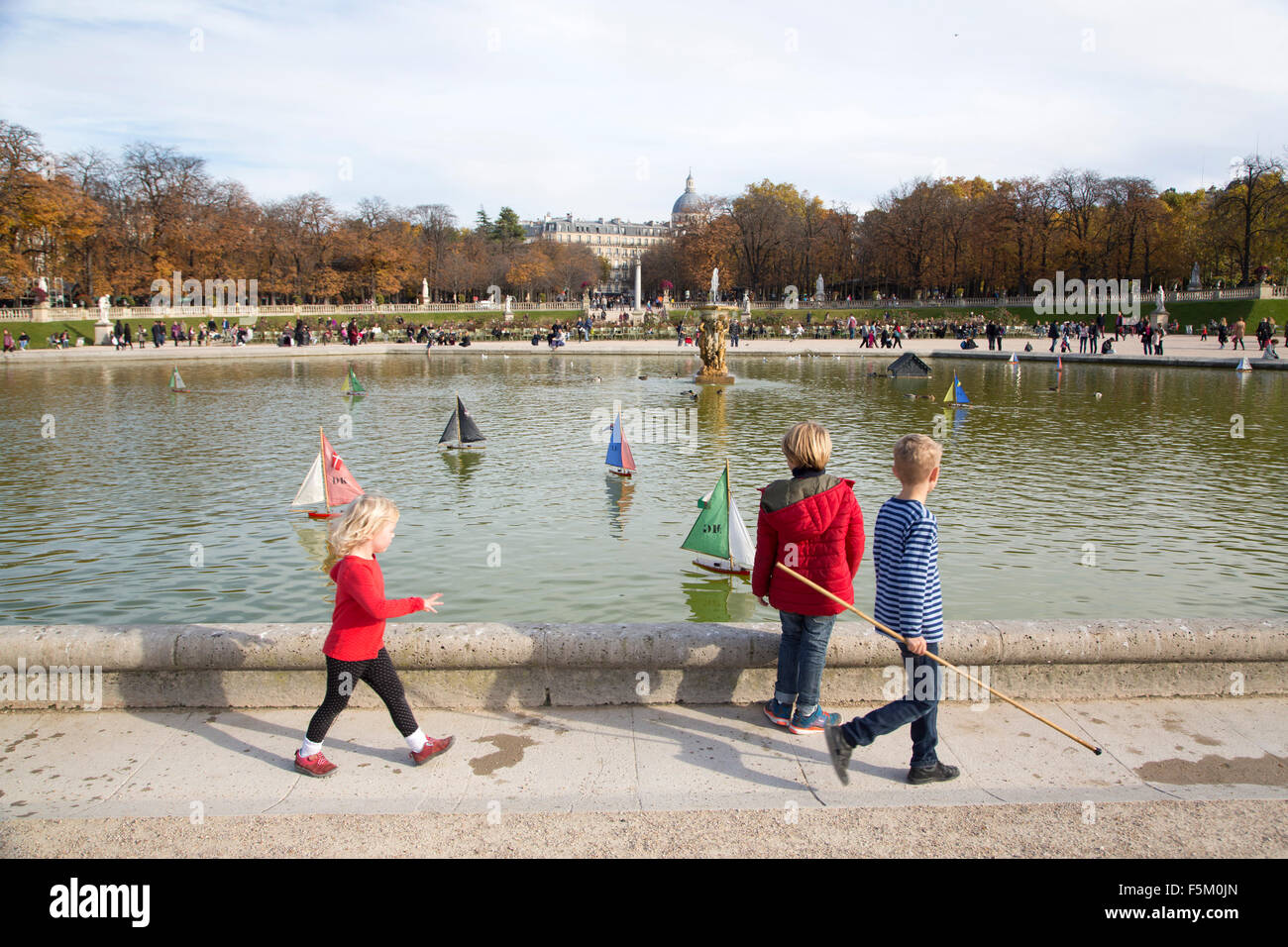 children playing with traditional sailing boats in jardin du luxembourg - Stock Image