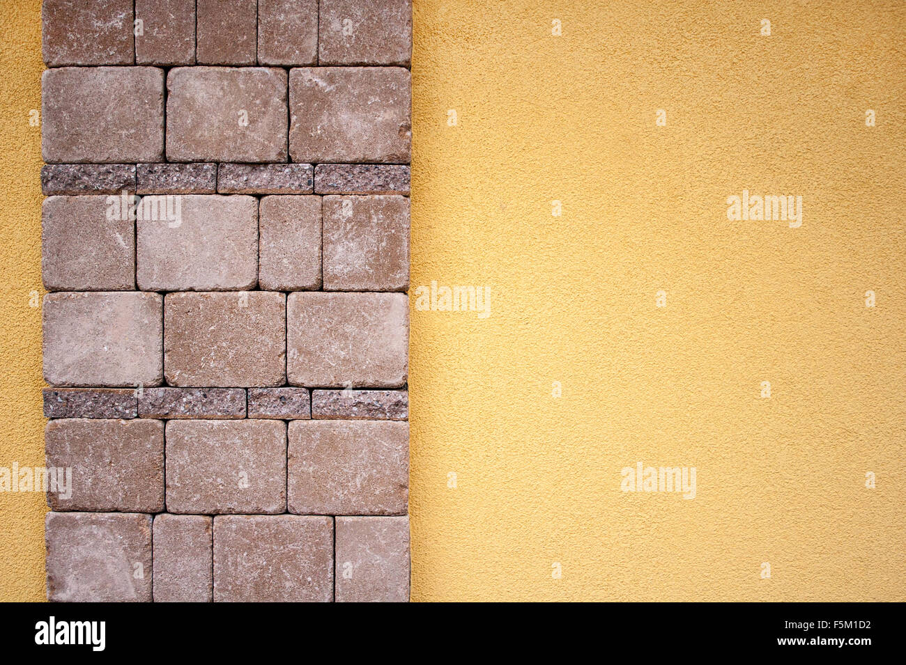 Yellow concrete wall with stone design on the left side Stock Photo ...