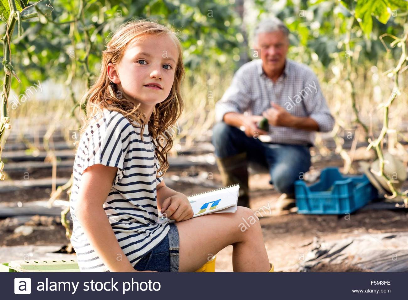 Girl sitting drawing while grandfather works looking at camera - Stock Image