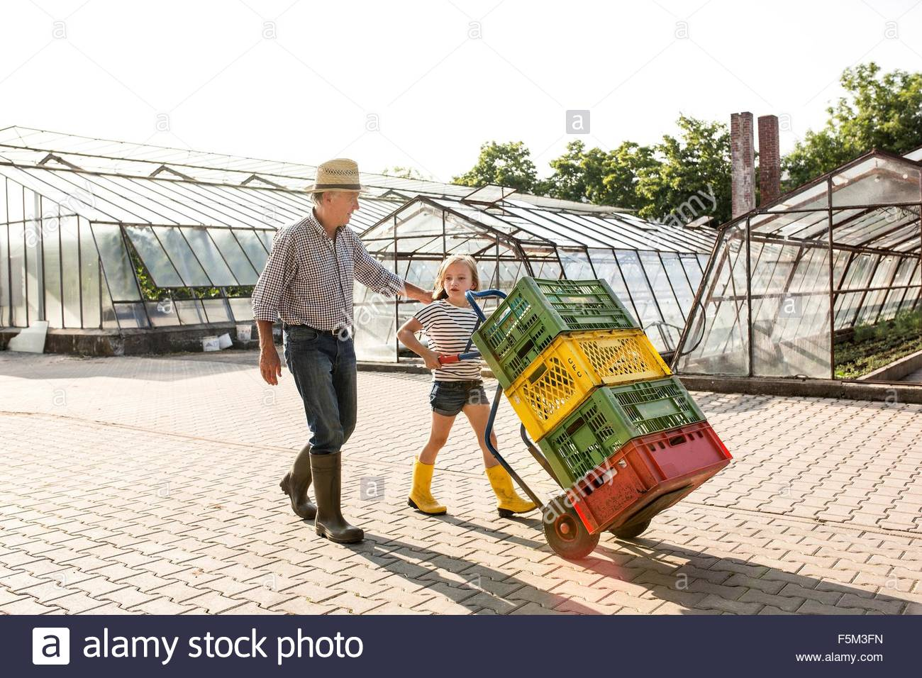 Grandfather and granddaughter pushing sack barrow stacked with crates - Stock Image