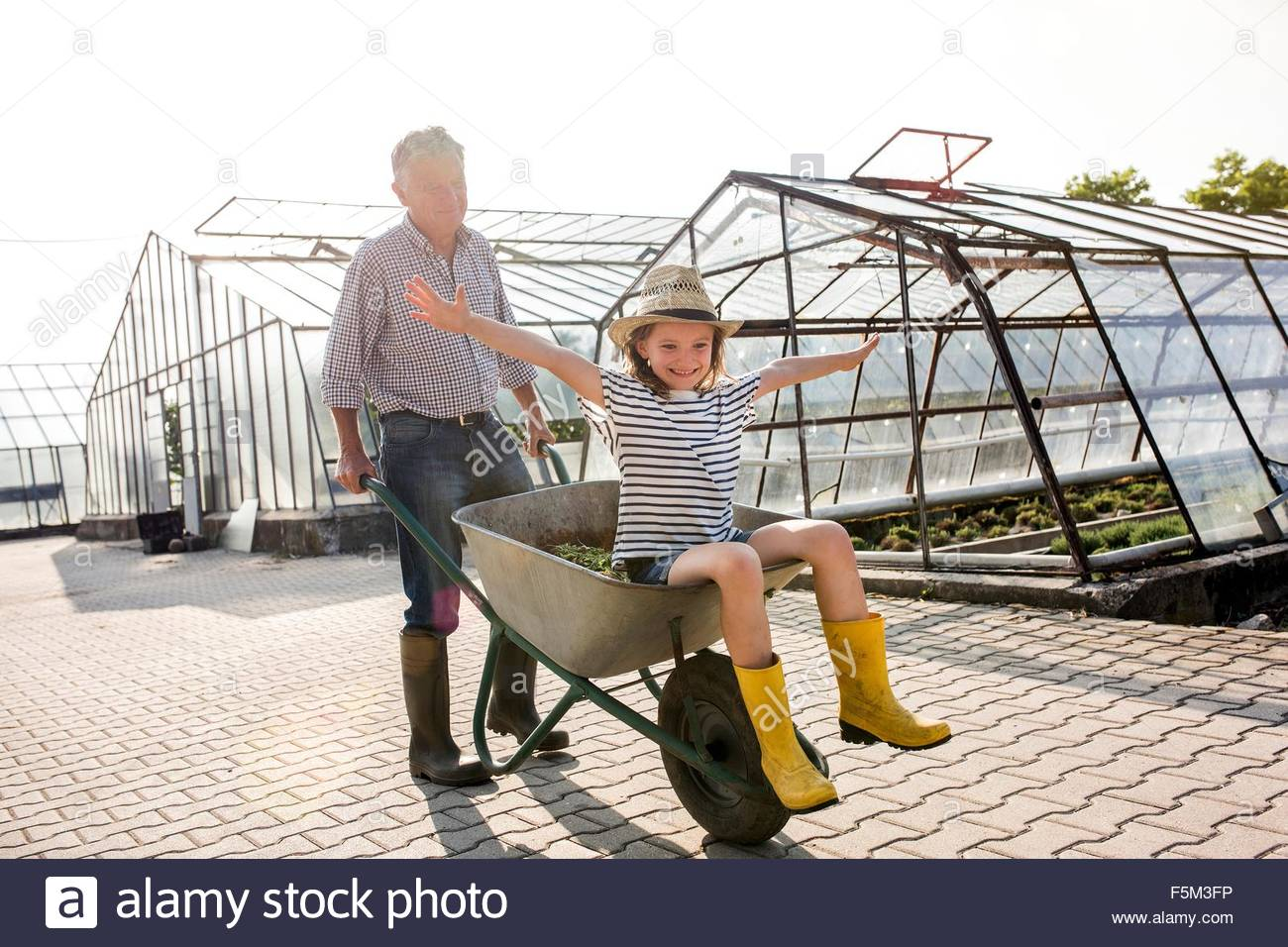 Grandfather pushing granddaughter in wheelbarrow, arms open looking at camera smiling - Stock Image